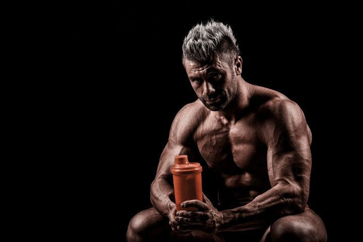 Guy taking BCAA supplement after working out
